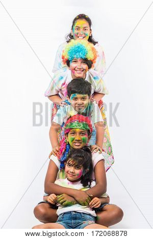 5 indian kids /friends /siblings celebrating Holi festival with and hands painted with gulal having copy space, isolated over white background