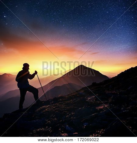 Happy man standing on a cliff. Fantastic starry sky and the milky way