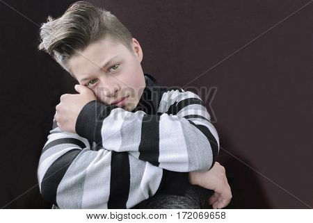 Portrait sad teenage boy on a dark background