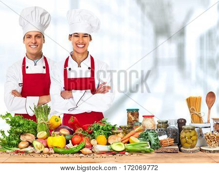 Group of young chefs on food vegetables background.