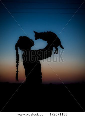 Silhouette of young girl and her little dog on sunset. Beautiful sky gradient.