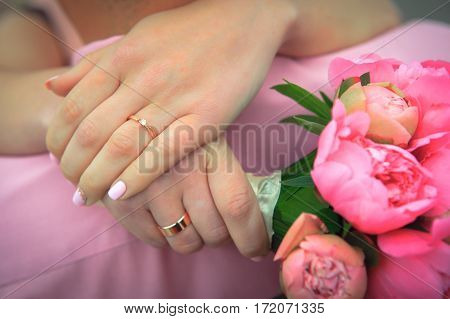 Beautiful hands of wedding couple. Wedding rings and flowers