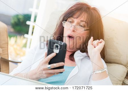 Shocked Middle Aged Woman Gasps While Using Her Smart Phone On The Patio.