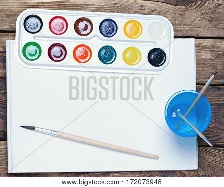 palette of watercolor paints, brushes and cup sheet of blank paper on a wooden surface.top view.toned.
