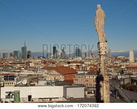 Sculpture, Milan and the Alps. Milan, Italy - June 13, 2015 Sculpture on the top of the cathedral in Milan and panorama of the city and the Alps.