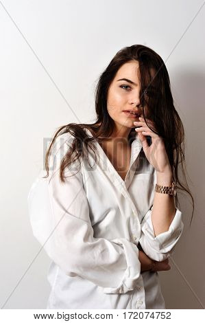 attractive sensual fashion model is posing in white shirt on white background