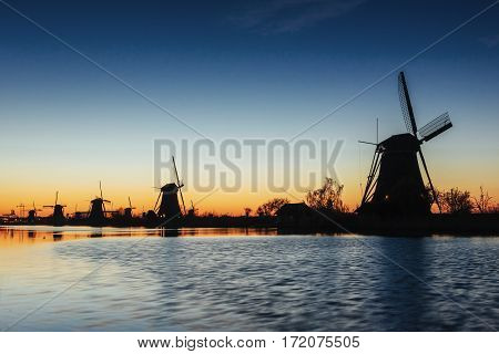 Fantastic sunset traditional Dutch windmills canal in Rotterdam. Wooden pier near the shore of the lake. Holland. Netherlands.