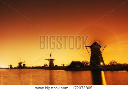Fantastic orange sunset traditional Dutch windmills canal in Rotterdam. Wooden pier near the shore of the lake. Holland. Netherlands.