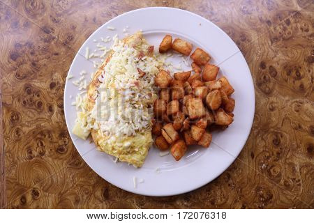 Omelet.  3 egg omelet with sausage, cheese, bacon, tomato's, hash brown potato's on a white plate on a burl wood table top.