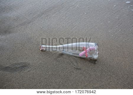 Message in a bottle. Romantic Love Note on Pink Paper with a Pink Ribbon in a wine bottle washed up on the shore in Maui Hawaii. Message of love. love notes.