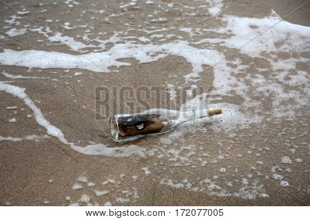 Message in a Bottle. Treasure Map in a bottle washed up upon shore. wine bottle with a treasure map in the waves and sand in Maui Hawaii.
