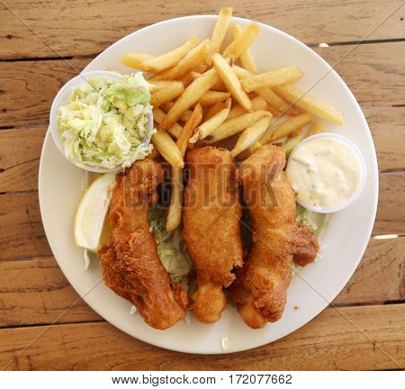 Fish & Chips. Mahi Mahi fish and chips with French fries and pineapple coleslaw on a white plate on a wooden table. Hawaiian Fish-n-Chips