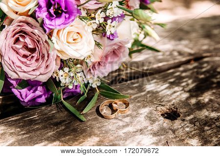 Wedding rings and lilac bouquet on wooden surface. Wedding rings