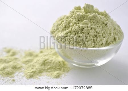Dried green pea flour - alternative gluten-free flour for baking and cooking, Isolated on white. Light green powder in a glass bowl on white background front view.
