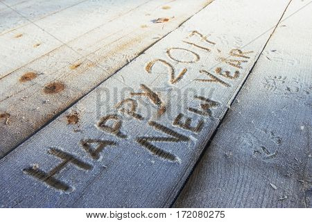 Writing on the snow. Wooden texture. On a wooden board. Happy New Year.