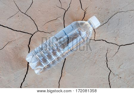 Bottle with pure water lies on the dried soil