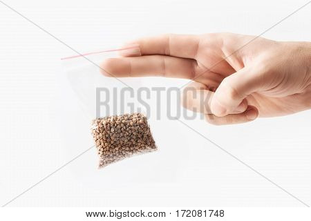 Hand holding Plastic transparent zipper bag with full of premium buckwheat groats isolated on white, Vacuum package mockup with red clip. Concept.