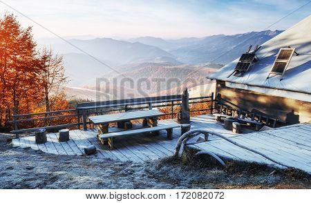 Carpathian mountain landscape with wooden farmhouse. October mountain beech forest with first winter snow. Carpathians, Ukraine, Europe