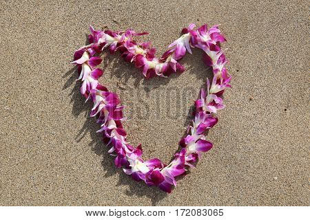 Hawaiian lei. Hawaiian lei on sand on the beach in a heart shaped designs.