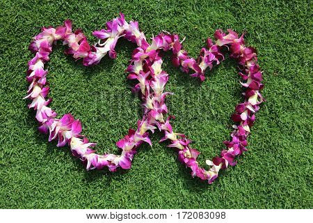 Hawaiian lei. two Hawaiian lei's on green grass in heart shaped designs.