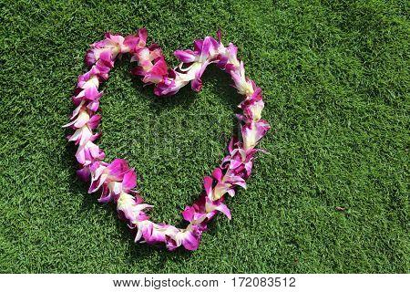Hawaiian lei. two Hawaiian lei's on green grass in heart shaped designs