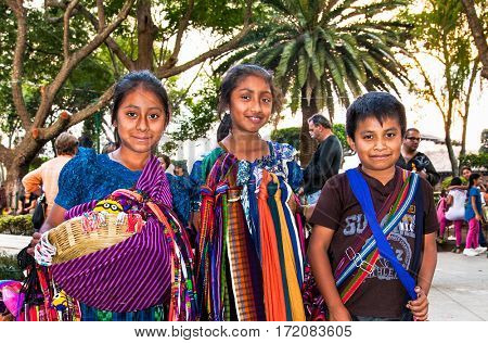 ANTIGUA, GUATEMALA-DEC 26, 2015: : Guatamalian children selling traditional  colorful fabric and goods at the street in Antigua, on Dec 26, 2015, Guatemala.