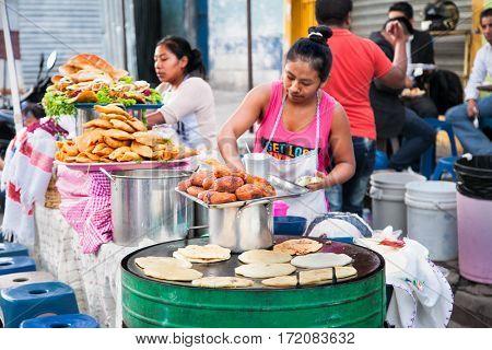 GUATEMALA CITY, GUATEMALA-DEC 25, 2015: Mayan women sell   Guatemalan food  at the street of Guatemala city on Dec 25 2015. Guatemala.