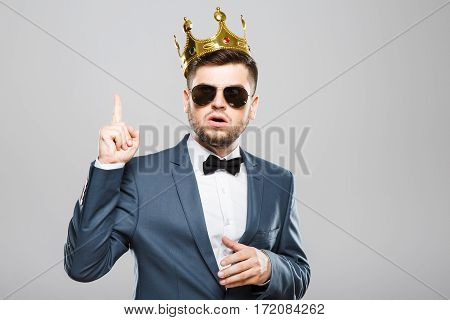 Stylish young man in suit with bow and sunglasses. Wearing crown. Having idea, finger raised. Outrageous, fancy look. Waist up, studio, indoors