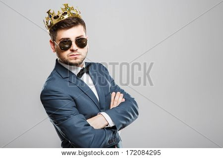 Serious man in suit with bow and sunglasses wearing crown. Hands crossed. Outrageous, fancy look. Waist up, studio, indoors