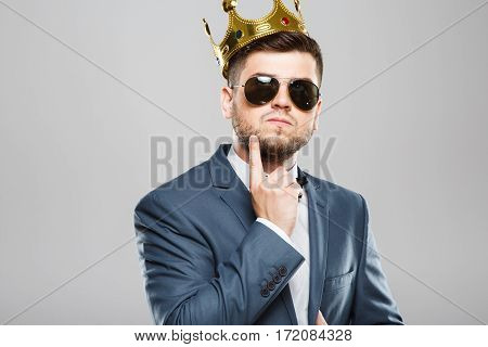 Stylish young man in suit with bow and sunglasses. Wearing crown. Thinking about something, thoughtfully looking up, touching chin. Outrageous, fancy look. Waist up, studio, indoors
