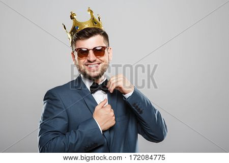 Stylish young man in suit with bow and sunglasses. Wearing crown. Looking at camera, touching bow and smiling broadly. Outrageous, fancy look, cool. Waist up, studio, indoors