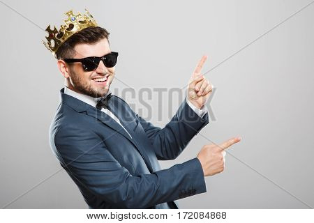 Stylish young man in suit with bow and sunglasses. Wearing crown. Having fun, dancing and smiling. Outrageous, fancy look, eccentric. Waist up, studio, indoors