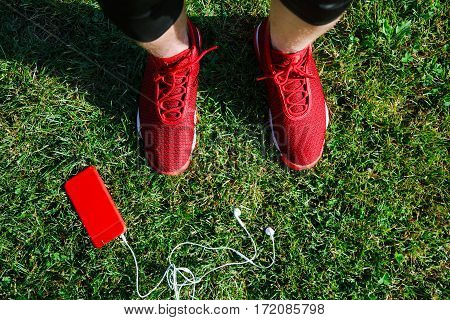 Sport concept, red sneakers for running and orange phone with walkmans lying on grass. Legs in professional sport shoes, no face, closeup.