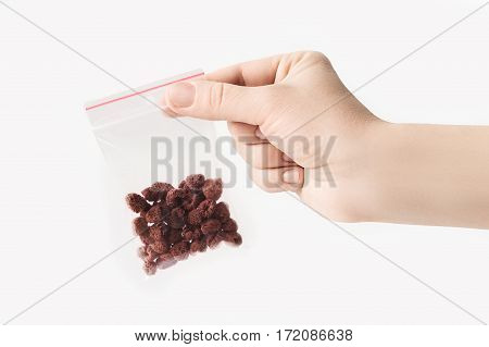 Hand holding Plastic transparent zipper bag with home dry raspberries isolated on white, Vacuum package mockup with red clip. Concept