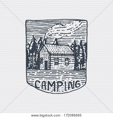 vintage old logo or badge, label engraved and old hand drawn style with mountains peak above forest and house.