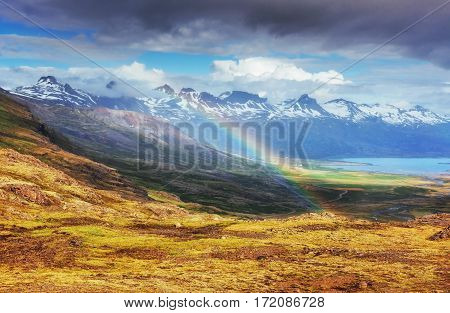 Fantastic views of the mountains and a little rain and a rainbow in Iceland. Colorful colors. Dramatic cumulus clouds. Europe.