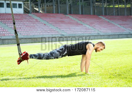 Man standing in plank position with training loop. Muscular sportsman catching training loop with legs, leaning on hands. Full body, horizontal position, outdoors, stadium