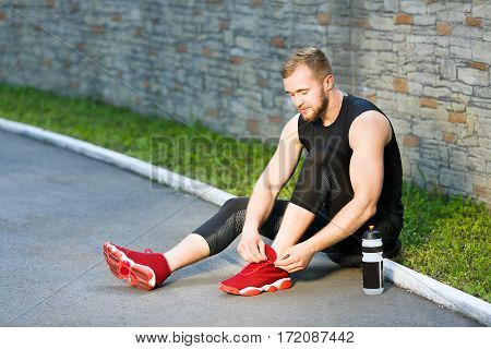 Man sitting and tightening lacings of red sneakers. Sportsman resting after training, bottle with water standing next to him. Full body, outdoors