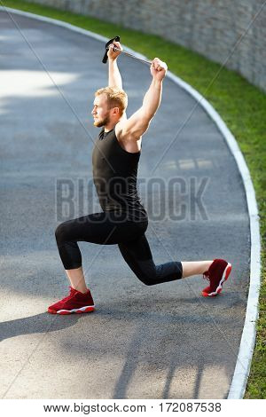 Profile of man training with expander. Muscular sportsman lunging with expander, hands up, leaning on one knee. Sport, outdoors, stadium, full body, vertical