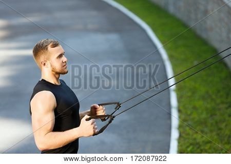 Profile of man training with expander hooked on fence. Muscular sportsman pulling expander to himself and looking ahead. Sport, outdoors, stadium, waist up