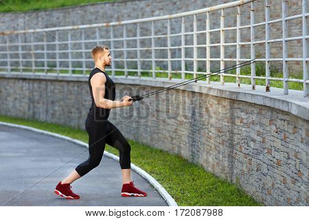Profile of of man training with expander hooked on fence. Muscular sportsman pulling expander to himself. Sport, outdoors, stadium, full body