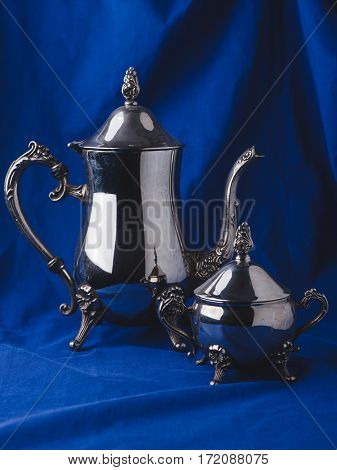 classic still life - jug teapot with sugar bowl on blue drapery fabric with pleats background