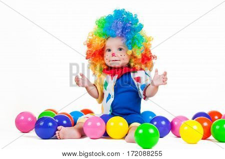 Child clown with a red nose and multicolored wig in with toy balls on a white background.