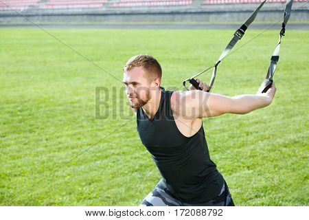 Profile of man training with training loop. Muscular sportsman holding training loop with both arms, lunging and looking forward. Waist up, outdoors, stadium