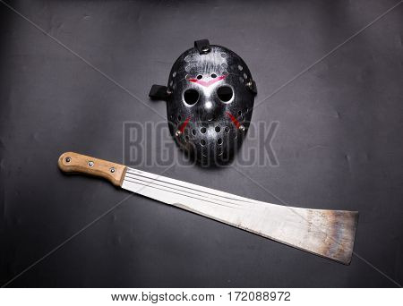 Murderer hockey mask and machete isolated on black