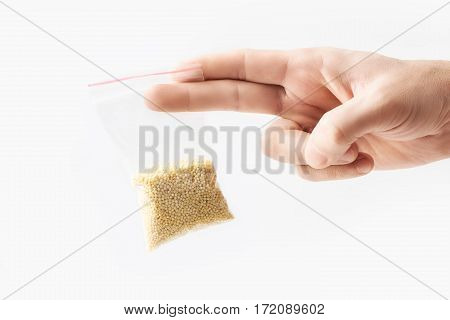 Hand holding Plastic transparent zipper bag with half raw millet groats isolated on white, Vacuum package mockup with red clip. Concept.