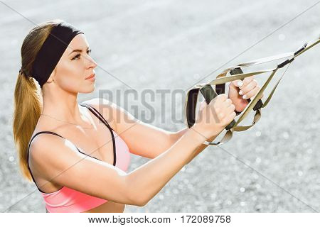 Sport, exercises with training loop outdoors. Profile of girl in rose top doing exercises with training loop on stadium. Sporty girl in good shape, waist up, closeup, side view
