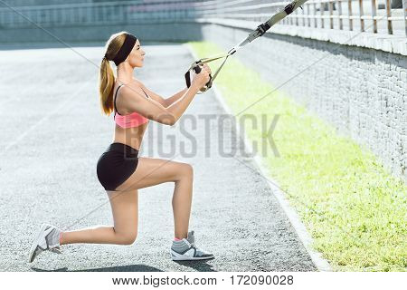 Sport, exercises with training loop outdoors. Profile of girl in rose top and back shorts doing exercises with training loop on stadium. Sporty girl in good shape squatting on one leg, full body, closeup
