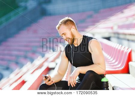 Man taking stop after running on track, looking at phone. Profile of sportsman in black training suit sitting on tribune of stadium. Outdoors, stadium, sunlight, unfocused background