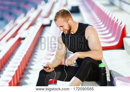 Man taking stop after running on track, looking at phone. Profile of sportsman in black training suit sitting on tribune of stadium and listening to music. Outdoors, stadium, sunlight